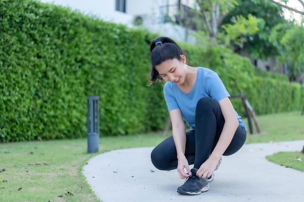 사톤 공원에서 달리기 전에 신발을 묶는 아시아 여성