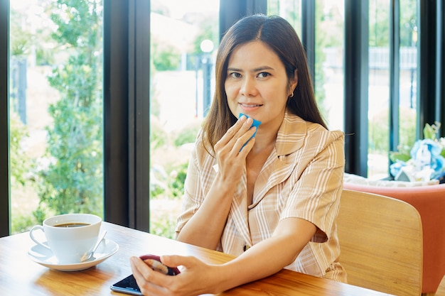 아시아 여성들은 클렌징 오일 필름을 사용하여 집 거실에서 얼굴 오일과 메이크업을 제거합니다. 부드럽고 건강한 피부. 뷰티 컨셉