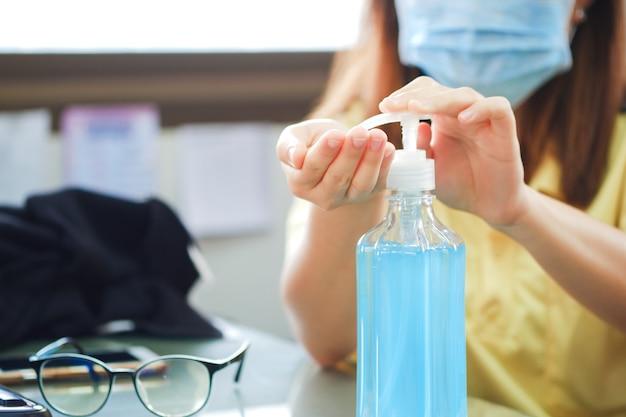 アジアの女性は、アルコール消毒ジェルを使用し、保護マスクを着用して、covid-19の発生の感染を防ぎます。コロナ予防。ウイルスはバクテリアとウイルスを根絶し、殺します。