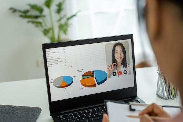 아시아 여성은 컴퓨터를 사용하여 화상 회의를 통해 팀과 온라인 채팅을합니다. 컴퓨터는 인터넷에 연결되어 동료와 함께 작업하고 작업 계획을 참조합니다.