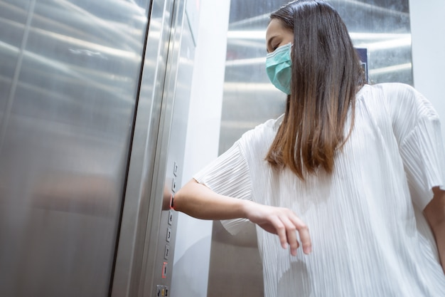 Азиатские женщины используют локти, чтобы нажимать кнопку лифта, чтобы избежать использования рук.