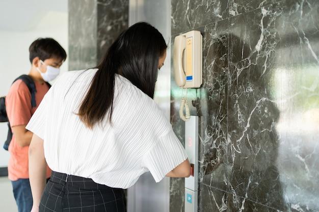 아시아 여성은 팔꿈치를 사용하여 엘리베이터 버튼을 눌러 손 사용을 피합니다.