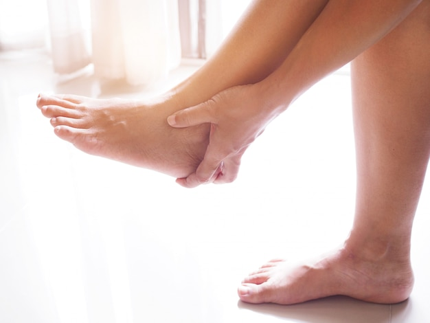 아시아 여성은 발목 통증, 만성 통증으로 발 부상으로 발 뒤꿈치를 마사지하기 위해 손을 사용합니다.