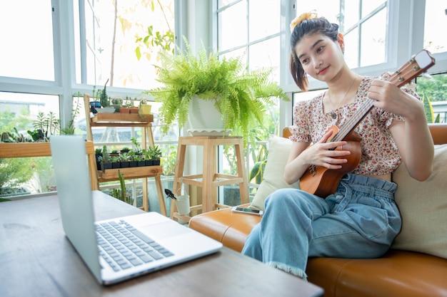 アジアの女性はノートパソコンを使用して、自宅でインターネット上でウクレレを演奏し、練習しています。