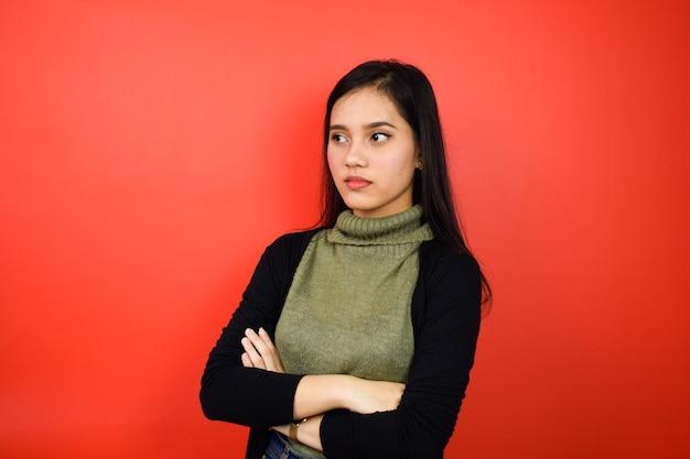 黒のセーターを使用して腕を組んで、赤い孤立した背景で側面を見ているアジアの女性
