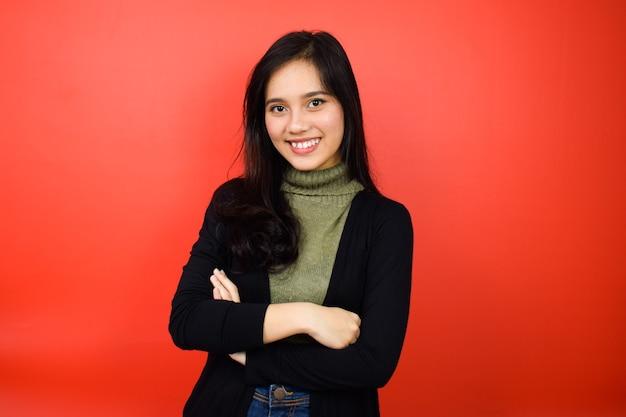 黒のセーターを使用してアジアの女性は腕を組んで、赤い孤立した背景で笑顔