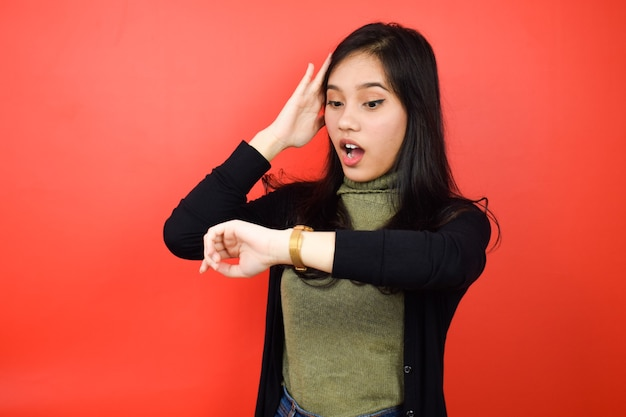 Asian women using black sweater looking at a watch and shocked with red isolated background