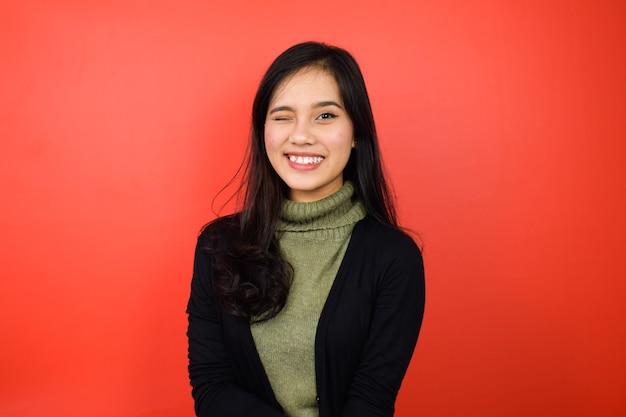 Азиатские женщины в черном свитере подмигивают и смотрят в камеру с красным изолированным фоном