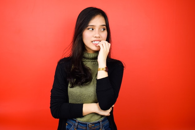 Asian women using black sweater worried and biting her nails and looking away isolated on red
