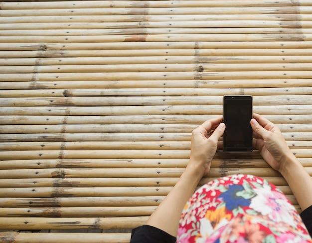 スマートフォン、暗い背景、クローズアップを使用してアジアの女性