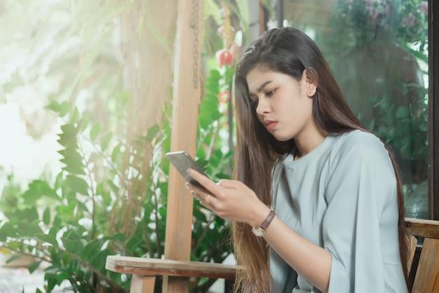 不安な顔のスマートフォンを使用しているアジアの女性