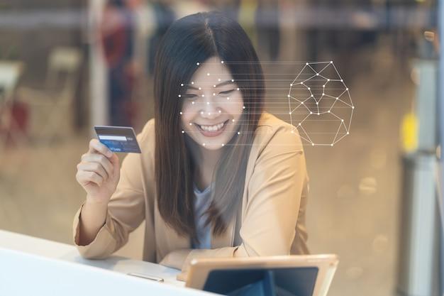 얼굴 인식을 통한 액세스 제어를 위해 기술 태블릿을 사용하는 아시아 여성