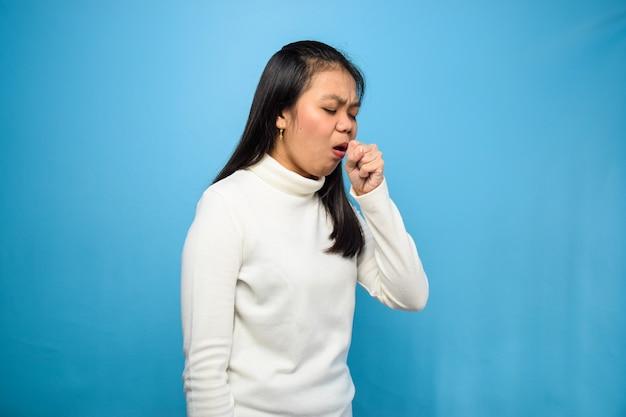 コロナウイルスの症状のために青い咳で隔離の白いtシャツを使用してアジアの女性