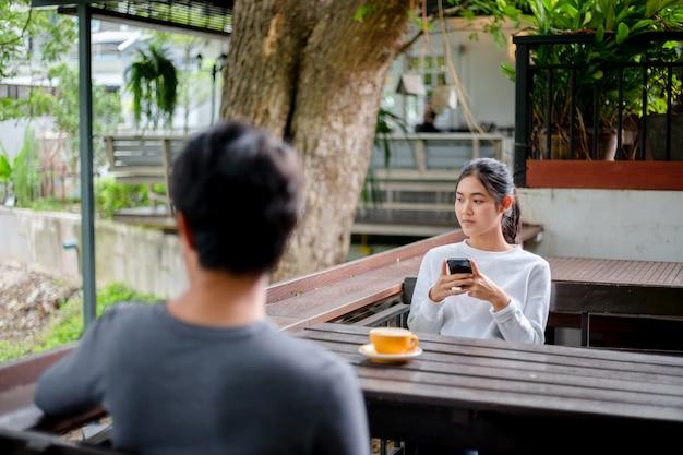 커피 숍에서 휴대 전화에 쓰기 메시지를 사용하는 아시아 여성
