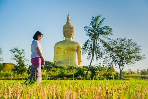An asian women walking and walking meditation the temple in the lawn behind a golden buddha image.