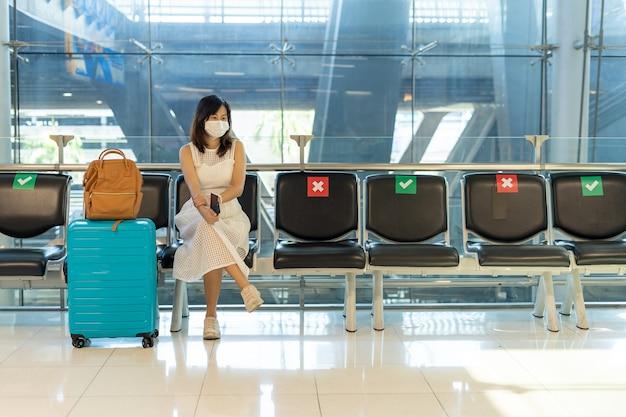 아시아 여성들은 코로나바이러스의 확산을 줄이기 위해 마스크를 쓰고 의자 사이에 앉습니다. 코로나19 사태로 관광객들이 비행기를 타기 위해 기다리고 있다.