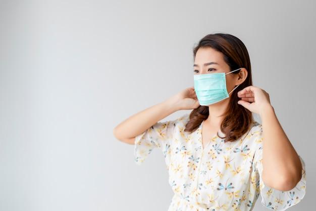 アジアの女性は、covid 2019の蔓延を防ぐために、美しい花柄のシャツとフェイスマスクを着用しています。ヘルスケアのコンセプト