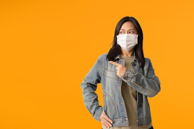 Азиатские женщины носят медицинскую маску для лица, показывая что-то на пустом месте, изолированном на желтом фоне