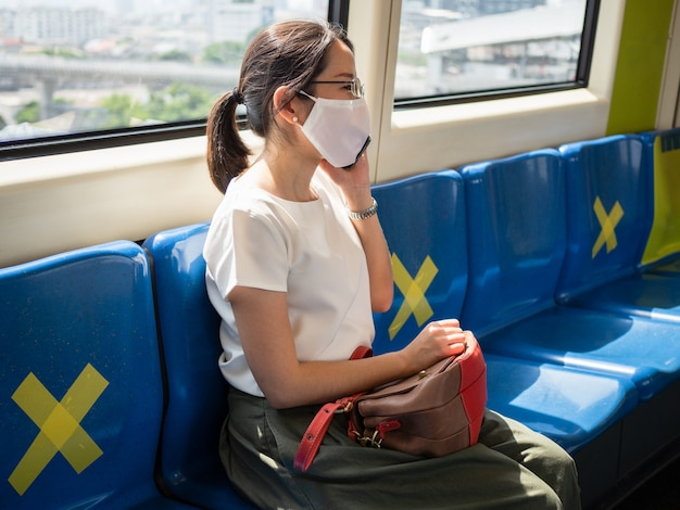 Asian women wear medical face mask, sitting on metro distance for one seat from other people, as new normal trend and self-protection against covid19 infection.