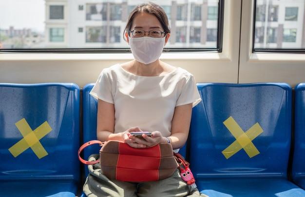 Азиатские женщины носят медицинскую маску, сидя на метро на расстоянии одного места от других людей