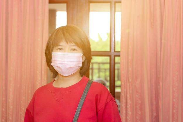 アジアの女性は家を出る前にサージカルマスクまたはフェイスマスクを着用し、covid-19からの感染を減らします