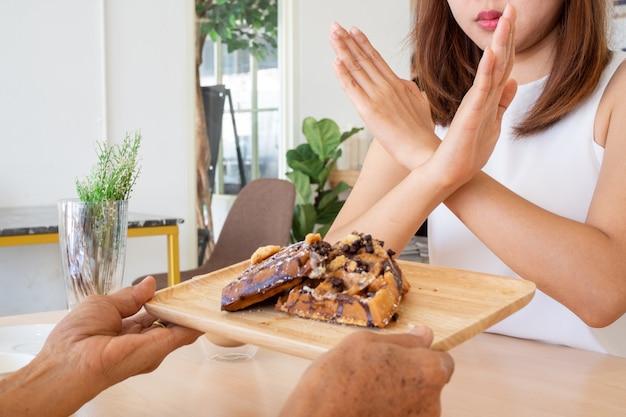 アジアの女性は白いシャツを着ており、友達が送ってくれるお菓子を拒否しています。減量するつもりです。
