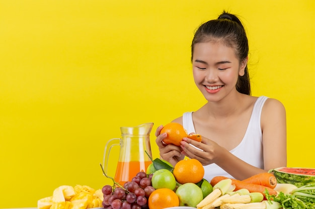 Asian women wear a white tank top. holdingorange and a table full of many fruits.