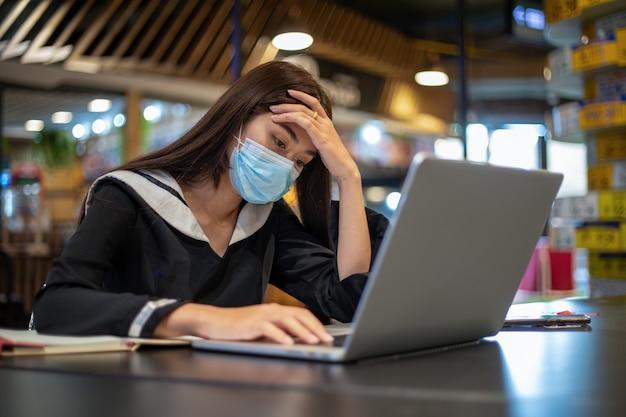 マスクをかぶったアジアの女性は、ノートパソコンを使ってオンラインで仕事や勉強をすることに真剣に取り組んでいます。