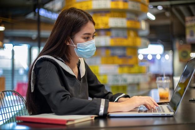 マスクを身に着けているアジアの女性と彼女は彼らのノートパソコンでオンラインで働いて勉強しています。