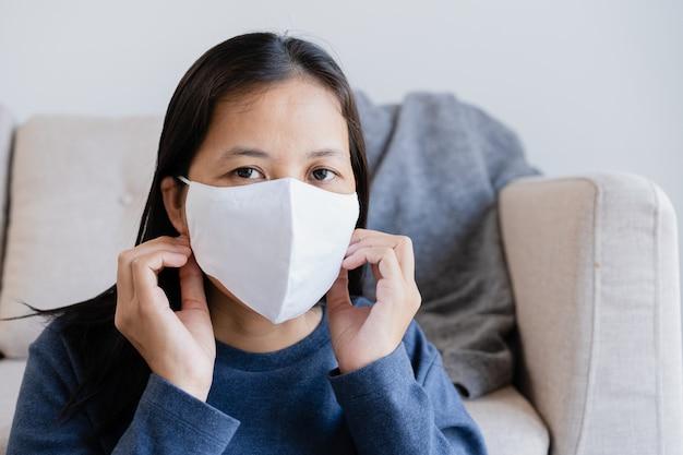 自宅のリビングルームでインフルエンザやcovid-19の流行の防護マスクを身に着けているアジアの女性