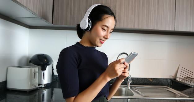ヘッドフォンを着用し、自宅のキッチンで音楽を聴いているアジアの女性