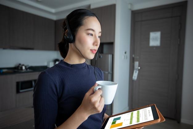 헤드폰을 착용하고 디지털 태블릿을 사용하는 아시아 여성