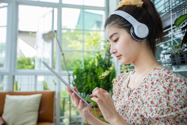ヘッドフォンを着用し、携帯電話とデジタルタブレットを使用して自宅でリラックスした日に音楽を聴いたり歌ったりするアジアの女性