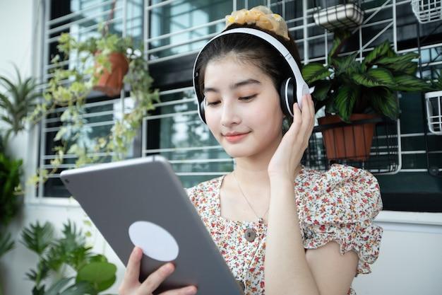 ヘッドフォンを着用し、携帯電話とデジタルタブレットを使用して、自宅でリラックスした日に音楽を聴いたり歌ったりするアジアの女性