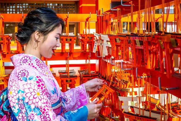 Donne asiatiche che indossano kimono tradizionale giapponese che visitano il bello nel santuario di fushimi inari a kyoto, giappone