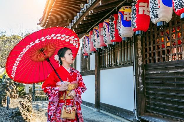 교토의 아름다운 곳을 방문하는 일본 전통 기모노를 입은 아시아 여성.