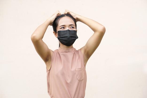 Азиатские женщины в масках положите руку на голову, потому что вы злитесь