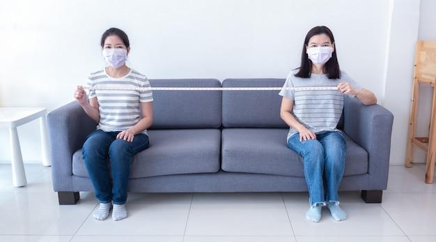 マスクを身に着けているアジアの女性がソファーに間隔をあけて座り、コロナウイルスの拡散を減らすために社会的な距離を測るための測定テープを持っています