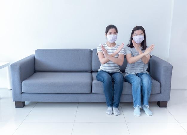 マスクを身に着けているアジアの女性はスペースのないソファーに一緒に座り、コロナウイルスの蔓延を減らすために社会的距離のサインを横断する