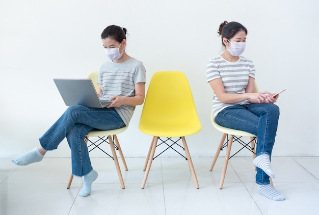 Asian women wearing masks working at home using notebook and smartphone to reduce spreading of coronavirus infection during covid-19 outbreak.