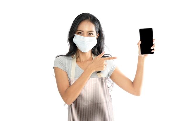 Азиатские женщины в медицинских масках от гриппа и фартуках. она указала пальцем на смартфон.