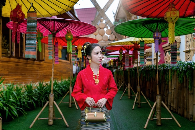 タイのナン省の有名な場所でタイの文化に従って伝統的なタイのドレスコスチュームを着ているアジアの女性。翻訳:「ようこそ」