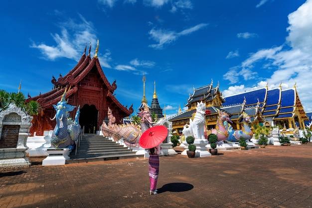 チェンマイの寺院でタイ文化に従って伝統的なタイのドレス衣装を着ているアジアの女性