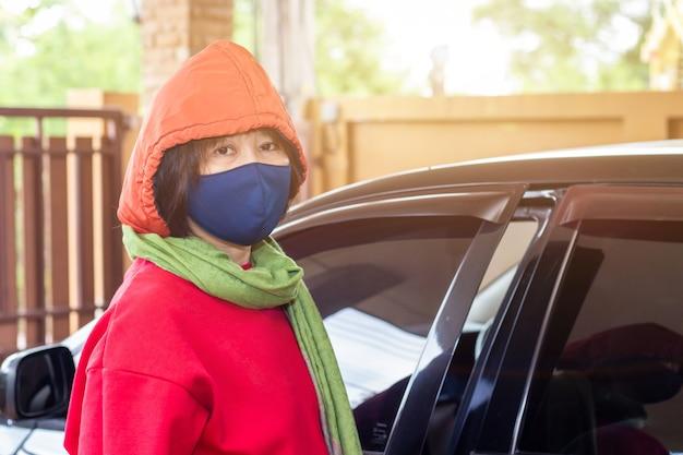 아시아 여성들은 집을 떠나기 전에 수술을 입고 covid-19로 인한 감염을 줄입니다.