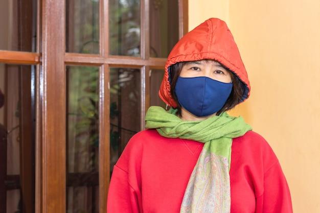 아시아 여성들은 집을 떠나기 전에 수술 용 마스크를 쓰고 코로나 19 감염을 줄입니다