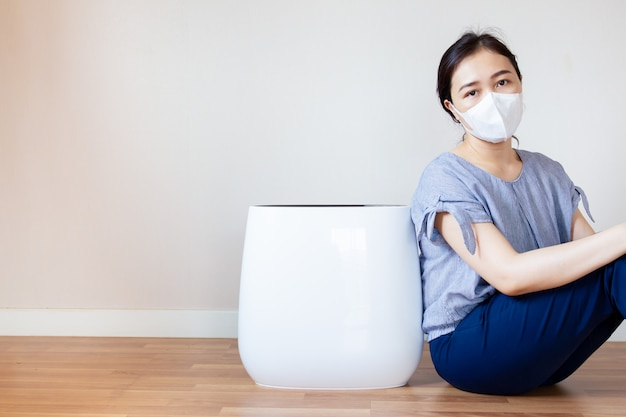 Asian women who has a health problem from air pollution in her house sitting beside the air purifier machine in the living room on the wooden floor