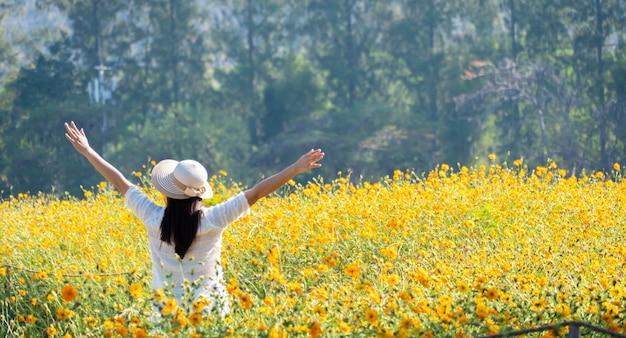 정원에 꽃이 만발한 아시아 여성. 신선한 봄과 여름 꽃 초원입니다.