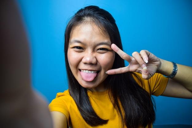 青い孤立した背景を持つアジアの女性は、自分撮りを取り、平和または勝利のサインを笑顔