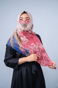 히잡과 세련된 얼굴 마스크를 쓴 아시아 여성들은 회색 배경에 대해 카메라를 바라보고 있다