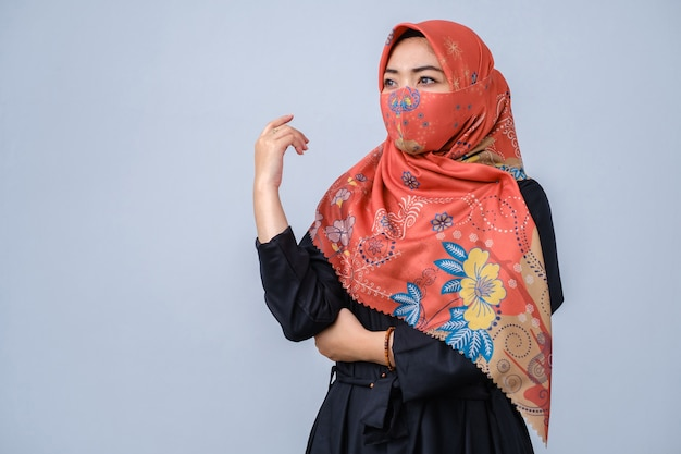 Asian women with hijab and fashionable face mask posing look to camera against grey background
